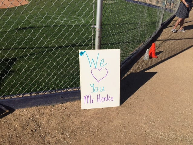 A sign showing the school's love for deceased baseball coach Greg Henke was left behind the backstop Monday for the school's first game since the coach's death Thursday.