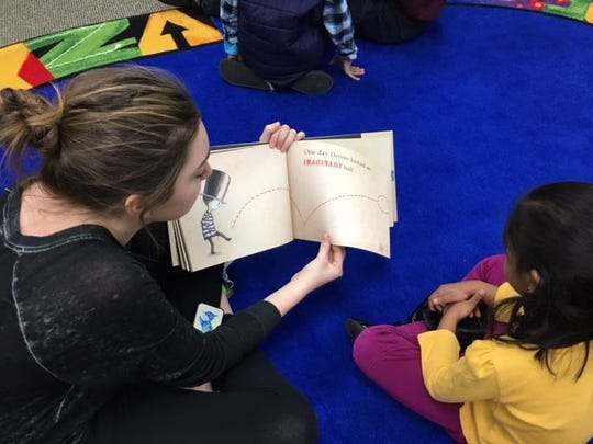 Teens promote reading for younger children during a Random Act of Kindness event in March 2016.