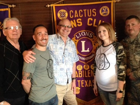 """Abilene Cactus Lions Club member Hal Griffin (left) presents a """"thank you"""" to Dyess We Care Team founder Gordon Story (center) and other team members."""