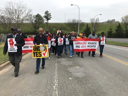 Labor union and others march toward a Nissan dealership