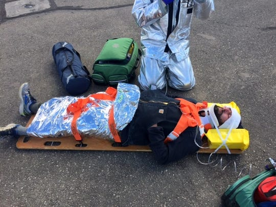 "A ""victim"" of the staged airplane crash is stabilized and loaded onto a gurney for transport to the hospital."