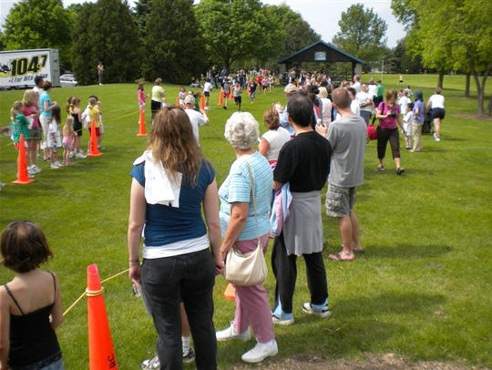 """Community members cheer on young runners at the """"It's"""