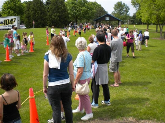 "Community members cheer on young runners at the ""It's Fun to Run."""