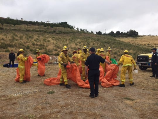 Firefighters at the Ronald Reagan Presidential Library & Museum in Simi Valley demonstrate the use of bags to shelter them from a wildfire Wednesday.