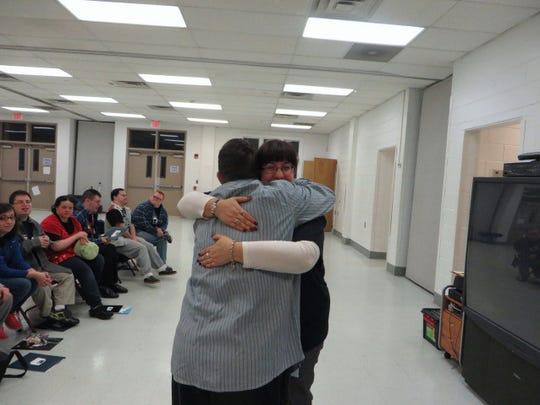 Debbie Goncalves hugs a member of Ta-Da! for a job