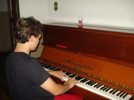 Rafael Pereira plays his new piano that he bought by selling candy in Brazil.