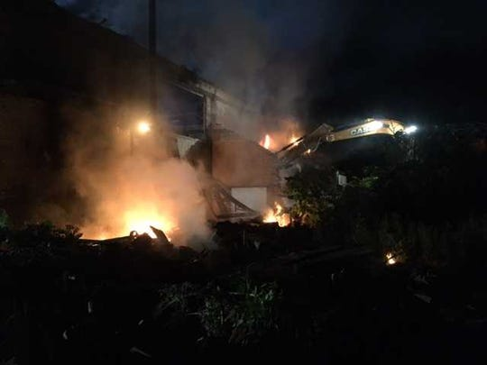 Working by firelight, contractor Art Groff demolishes