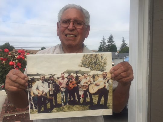 Cruz Espinoza poses with his prize possession, a copy of a photo of himself and his bandmates with President Reagan in 1984. He recently left the original White House-issued print in a black album at the Walmart in Oxnard and hopes the finder will return it to him.