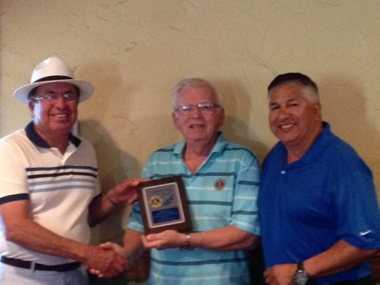Lion Lupe Chavez receives outstanding the Lion Award from PDG Hal Griffin and President Ozzie Trevino.