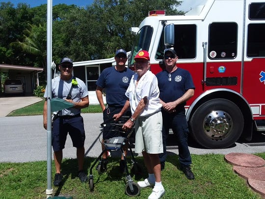 Iona-McGregor Fire Department firefighters Dan Drews, Rick Garcia and Paul Graham helped Ray Carlson, 95, center, raise his U.S. flag when the retired Marine and World War II veteran could not.