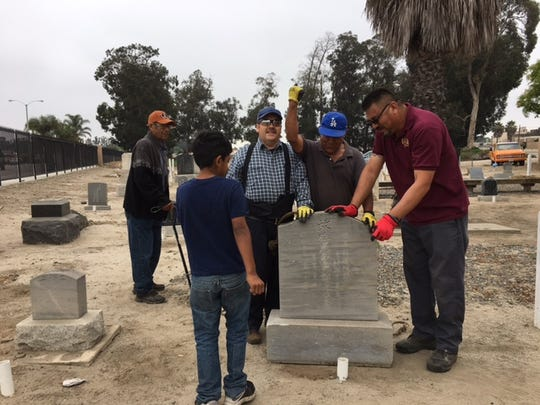 Adrian Diaz watches as workers, including his father, finish securing a headstone at the Japanese cemetery in Oxnard. From right are workers Enrique Diaz, Juan Perez and Armando Ruiz.