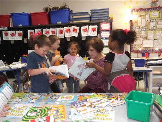 Barbara Pollack, of Altrusa, presents books to kindergarten