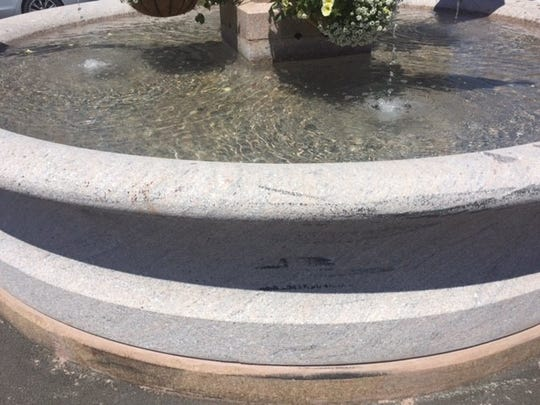 Black marks on the side of the new granite basin show where a vehicle struck the fountain.