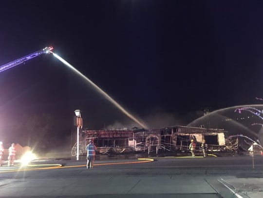Firefighters finish dowsing the flames after the empty