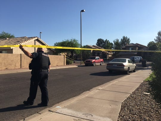 A Mesa police officer walks underneath crime tape near the scene of a fatal shooting in the 7300 block of East Monte Avenue on July 13, 2017.