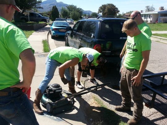 Volunteers get a lawn mower ready so they can help