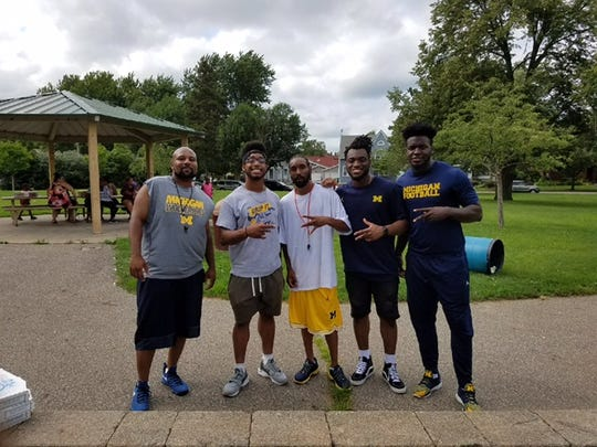 The Michigan Patriots are coached by Chris Montgomery, far left, and Jonathan Matthews, center. They are joined by U-M players, from left Chris Evans, Josh Uche and Nick Eubanks