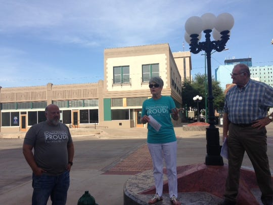 Cynthia Laney, center, speaks to members of the Downtown Steering Committee Thursday near 8th and Ohio - the thriving center of downtown development.