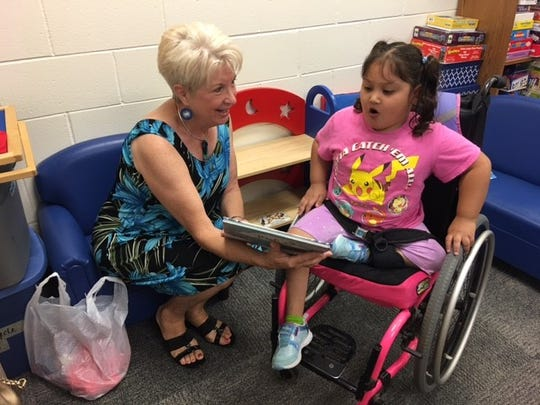 A volunteer works with a child during the United Way's ReadingPals program.
