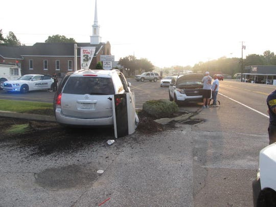 A damaged van sits on the side of East Main Street in Huntingdon after it was struck in a police chase Tuesday morning.