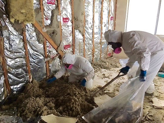 Employees of Disaster Kleenup Specialists do asbestos abatement at a triplex in Santa Cruz.