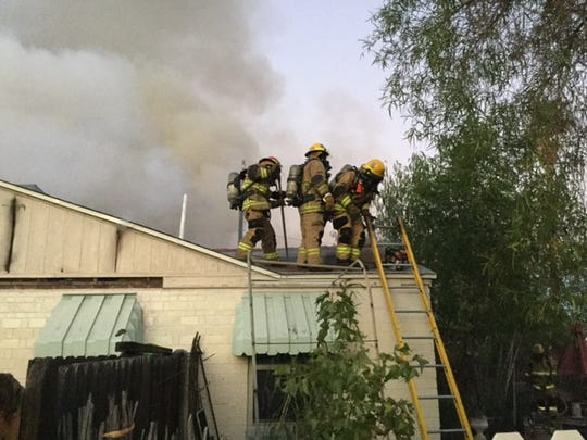 Fire crews fight a blaze that damaged two houses in north Phoenix on Aug. 9, 2017.