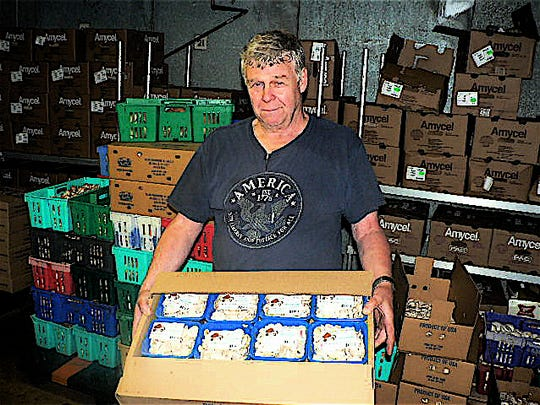Ned Palm readies a case of packages mushroom for for delivery.