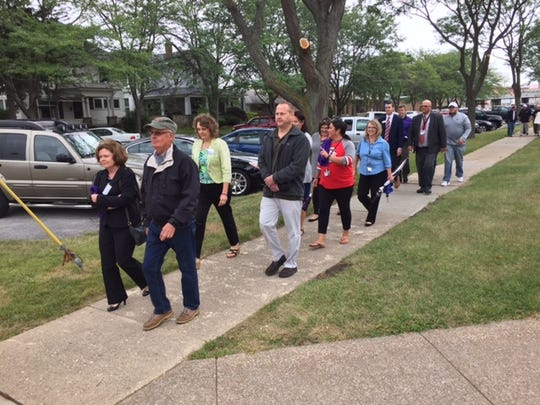 A group of Ottawa County residents and community leaders walk from the Ottawa County Courthouse to Light House Sober Living Thursday as part of the county's Overdose Awareness Day.