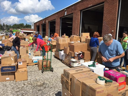 Volunteers organize boxes of goods donated for Hurricane Harvey relief. The donations, which filled ten tractor trailers, will be transported to Houston by Bailey Coach on Friday, September 8.