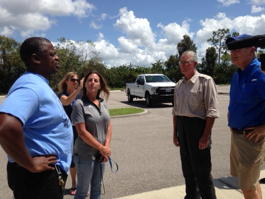 Congressman Francis Rooney, background right, meets with Dunbar High School officials, left, as they open the school to shelter evacuees after Irma.