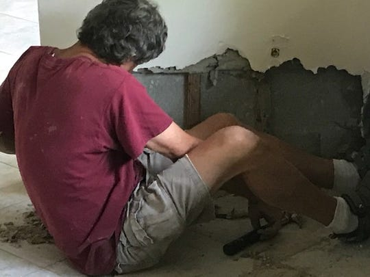 Bill Burdette removes drywall  after about two feet of water from the Orange River flooded  his Shady River Lane home on Sunday.