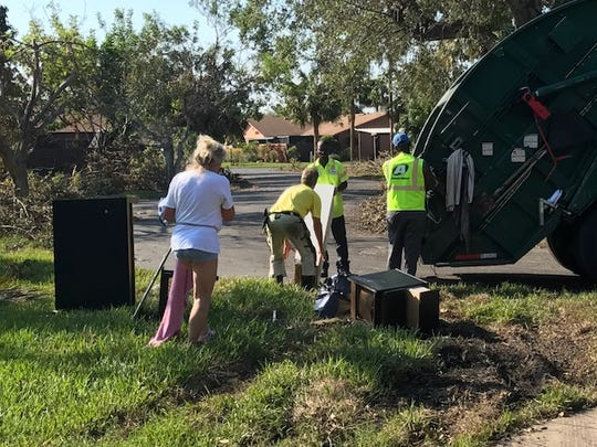 Bosse and Anneli Gaimer bring their belongings to a garbage truck in the Royal Woods development off of Island Park Road. The couple, from Sweden, could not get back to Southwest Florida before Irma hit.