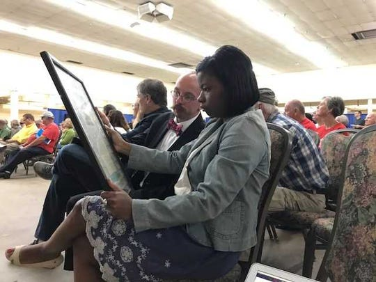 Councilman Brett Withers and Councilwoman Tanaka Vercher review language from the original bond of the Tennessee State Fair Board that was passed around Thursday.