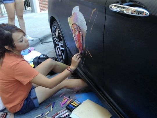 Staphany Garnica chalks a drawing of a Mexican vendor on a new Honda Accord during Saturday's Chalk the Block arts festival in Downtown El Paso.