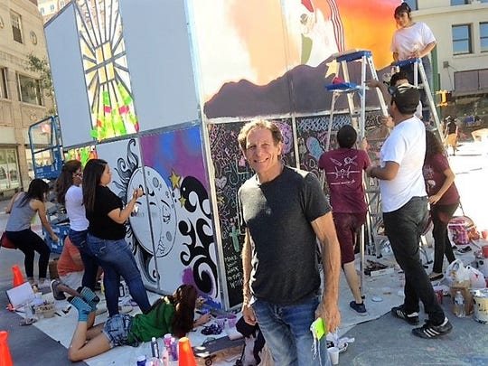 New Yorker Scott Cohen stands in front of his Life Cube Project while El Paso students paint murals on the cube at the Chalk the Block arts festival in Downtown El Paso.