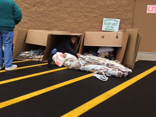 Angela Riley, the mens' case manager at Harmony House, Friday was making her bed inside a cardboard box at Walmart in Ontarion for the agency's annual fundraiser, Sleep Out for the Homeless.
