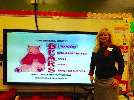 Kindergarten teacher Stacey Lee explains the school mantra, which is recited by the students at the beginning of each school day. In addition to the academic subjects, character education is taught in the curriculum.