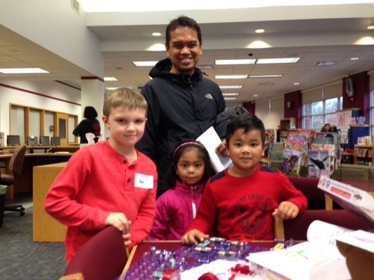 John Etzel, 8,  shows his circuit creation to Errimy Samad and his children Eadyn, 7, and Emilyia, 5. Building the circuit is part of the school's STEM curriculum.