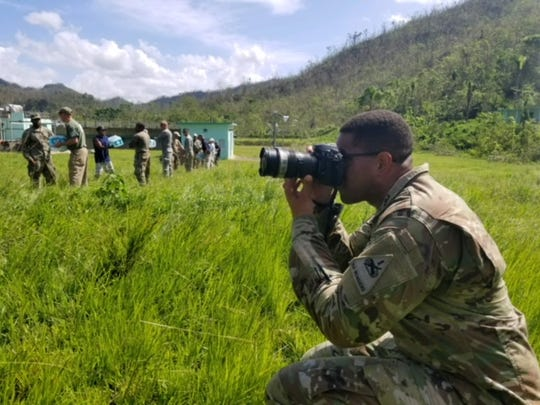 Sgt. Michael Eaddy, public affairs specialist with the 24th Press Camp Headquarters, takes photos of personnel unloading water from a helicopter in Utuado, Puerto Rico.