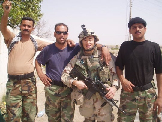 Yauo Yang poses with members of Iraqi security forces