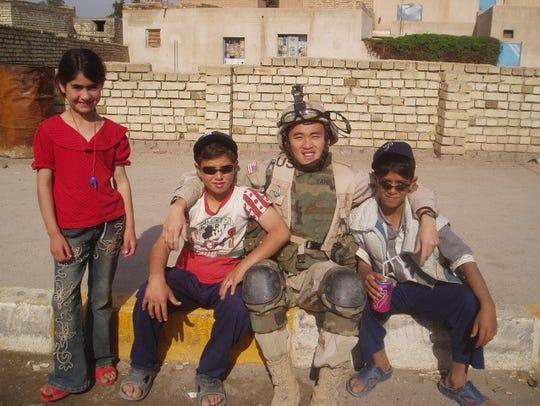 Yauo Yang sits with Iraqi children in Samarra.