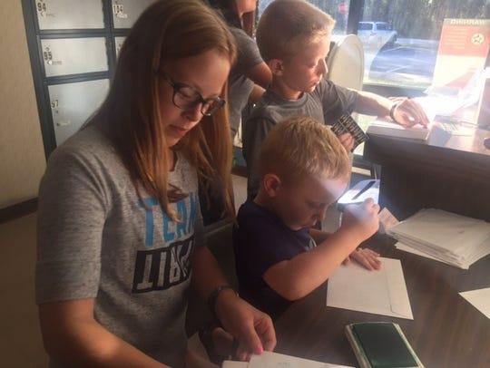 Siblings Ella Grace, Silas and Major Jordan stamp greetings