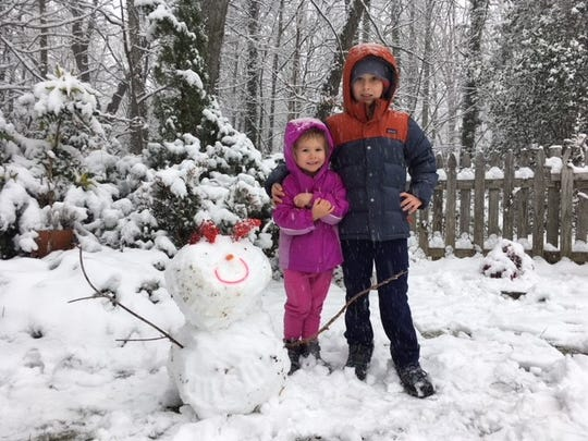 Newbies to Black Mountain, Rigby and Hannah Nicholson pose beside their snowman on McCoy Cove Road.