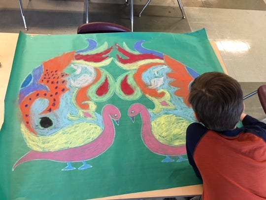 Wyatt works on his rangoli at a Milwaukee County Zoo