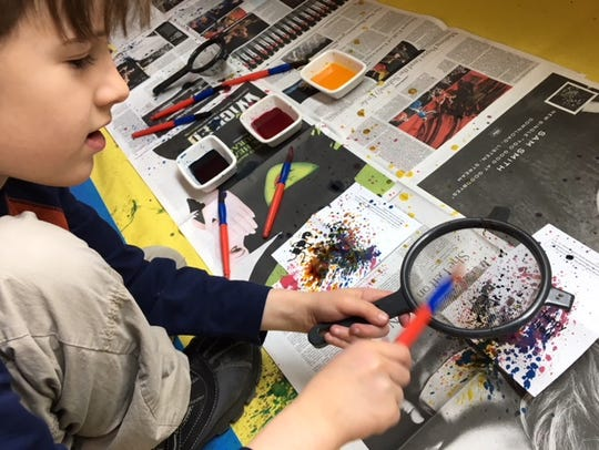 Wyatt sprinkles paint on his Holi card.