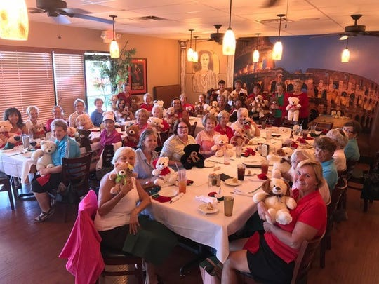Members of the Sandpiper Bay Women's Golf Association enjoy lunch at Roma's Pizzeria while holding the teddy bears they brought to donate to the Port St. Lucie Police Department.