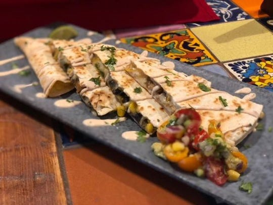 A vegetable quesadilla with mushrooms, corn, black beans, queso blanco and ranchero sauce from Cabos Cantina.