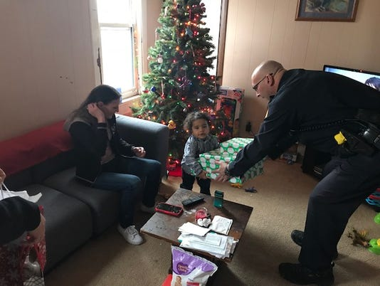 a little girl with a big present and a West Allis officer
