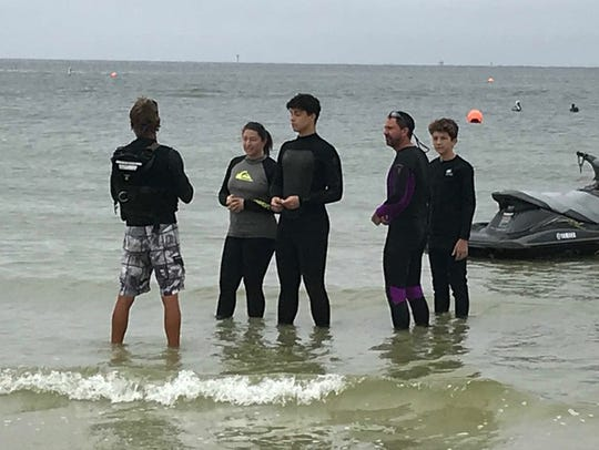 Todd Koszesza of Rebel Water Sports, instructs the Griffiths family of Virginia in jet ski use. The Griffiths, from left, Diana, William, John and Calvin, were heading out to view dolphins.