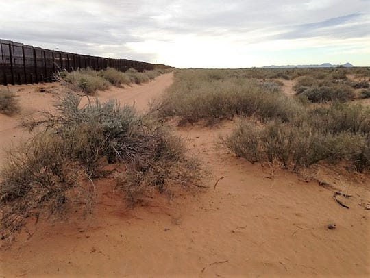 The U.S. government's iron border fence, left, stretches